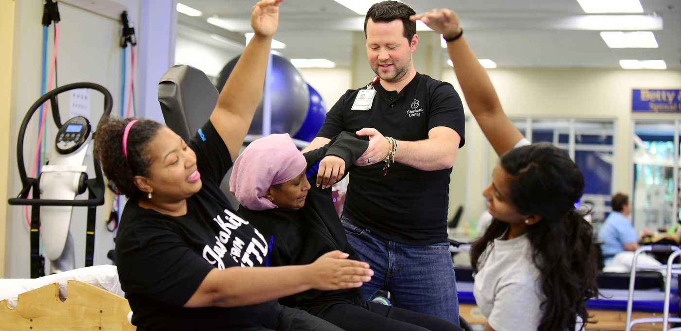Exercise physiologist assists multiple sclerosis patient during physical therapy.