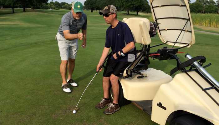 Adaptive golfer is coached on golf course during Health and Wellness Clinic