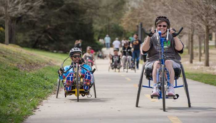 Two participants use adaptive bikes to participate in handcycling