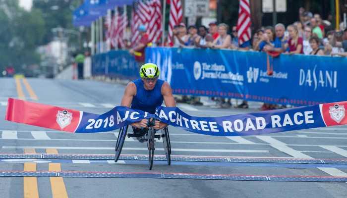 Wheelchair racer crosses AJC Peachtree Roadrace finish line, breaking through ribbon