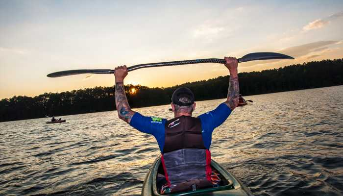 Man in kayak on lake holds paddle over his head.