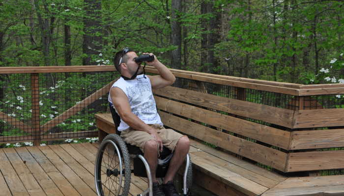 Wheelchair user on deck using binoculars to view birds.
