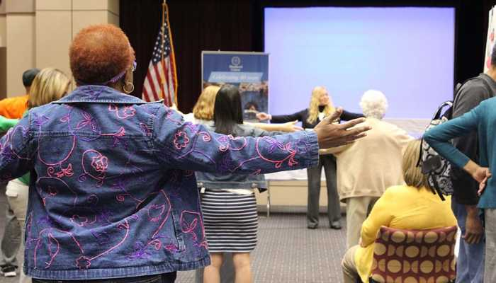 Participants stand with arms held out to practice balance at falls seminar.