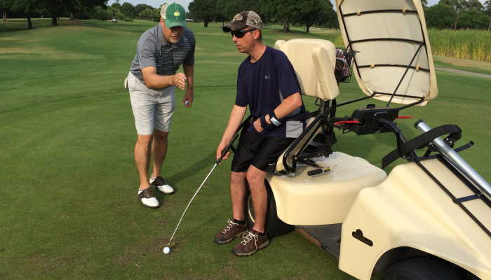 Participant uses adaptive equipment to golf.