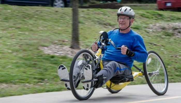 Man in helmet and cycling gear uses adaptive hand cycling bike.