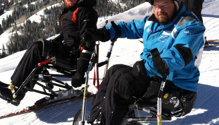Two ski trip participants on adapted skis prepare to take the slopes.